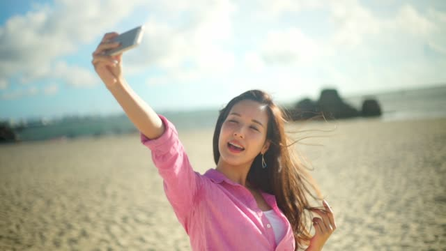 stockvideo's en b-roll-footage met japanese young female take selfie at the beach. - zelfportret fotograferen