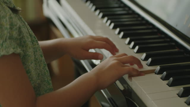 Japanese young girl playing piano at home.
