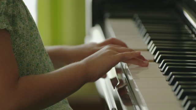 vídeos de stock e filmes b-roll de japanese young girl playing piano at home. - pianista