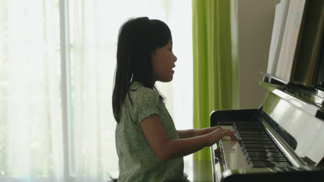 vídeos de stock e filmes b-roll de japanese young girl playing piano at home. - piano