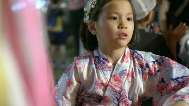 japanese young girl playing shateki (a shooting game) - yukata video stock e b–roll