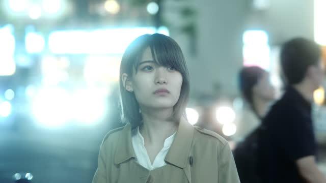 japanese young woman looks feel anxiety on night street - 不安点の映像素材/bロール