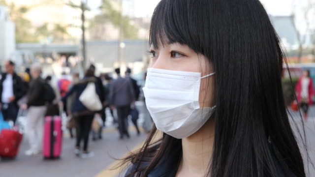 japanese young woman strolling in tokyo - mundschutz stock-videos und b-roll-filmmaterial