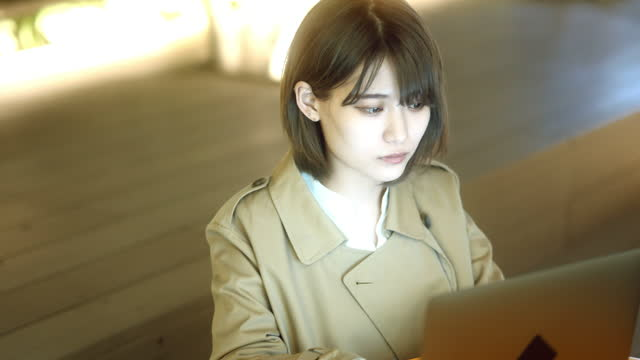 japanese young woman working with laptop on open terrace in night - loneliness点の映像素材/bロール