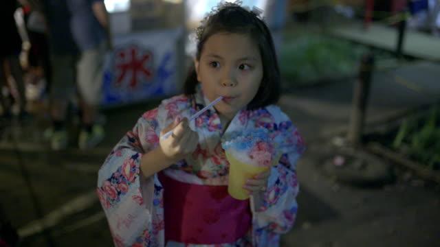 japanese young yukata girl eating kokigori a famous dessert in japan. - yukata video stock e b–roll