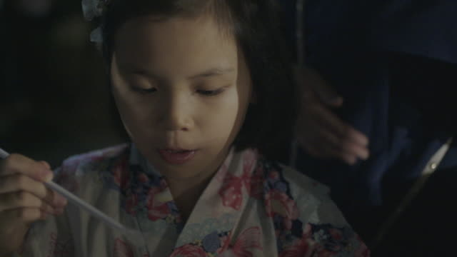 japanese young yukata girl eating kokigori a famous dessert in japan. - 伝統的な祭り点の映像素材/bロール