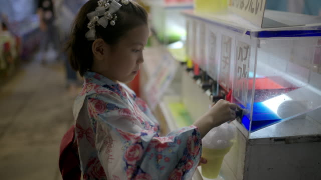 japanese young yukata girl put syrup on the kokigori a famous dessert in japan with her mother. - 伝統的な祭り点の映像素材/bロール