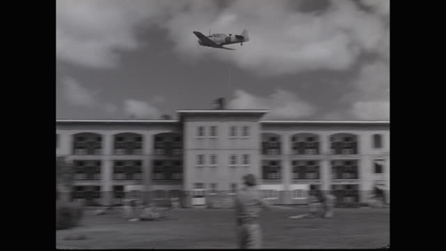 ws pan japanese zero fighter plane flying over military building / united states - fighter stock videos & royalty-free footage