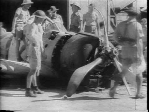 Japanese Zero flying with US Army insignia / military personnel inspecting wrecked zero plane inspecting the exterior of a functioning one / officer...