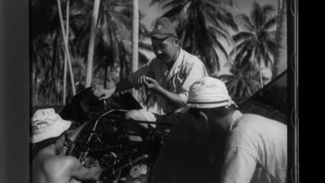 japanese zero recon seaplane returns to the seaplane base during world war ii; a ground crew works on engine maintenance; flight crews receive... - war stock-videos und b-roll-filmmaterial