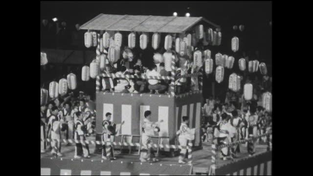 japan-u.s. goodwill bon festival dancers perform on a platform and on an athletic field as spectators watch. - yukata video stock e b–roll