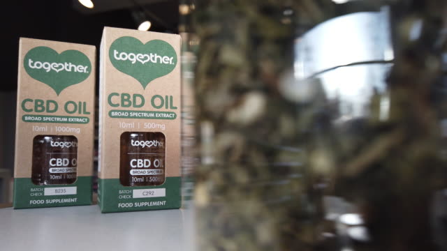"""jar of hemp leaves is seen next to two bottles of """"together"""" cbd oil in a branch of the health chain planet organic on february 17, 2020 in london,... - oil stock videos & royalty-free footage"""