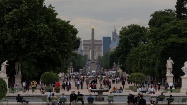 vidéos et rushes de ws jardin des tuileries with tourists walking and arc de triomphe in background / paris,paris,france - arc élément architectural