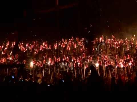 jarl squad with flaming torches surround their leader who is standing on the replica viking galley for the up helly aa festival - galeere stock-videos und b-roll-filmmaterial