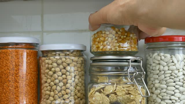 gläser mit hülsenfrüchten auf einem regal in der speisekammer der küche gefüllt sind von einem mann angeordnet. - equipment stock-videos und b-roll-filmmaterial