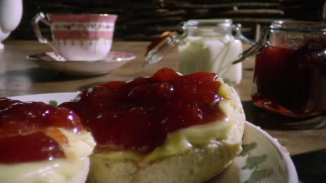 jars of cream and jam and scones on table, uk - indulgence stock videos & royalty-free footage