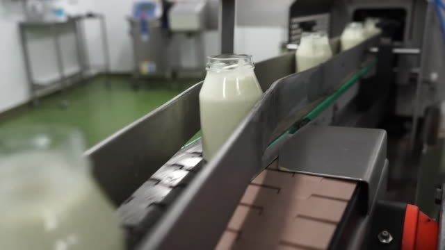 jars of cream on production line in factory, wiltshire - dairy product stock videos & royalty-free footage