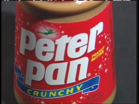 jars of peter pan peanut butter creamy and crunchy are displayed. - crunchy stock videos & royalty-free footage