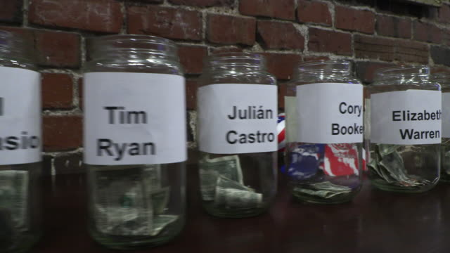 stockvideo's en b-roll-footage met jars with the names of candidates are lined up for a donation poll as democrats gathered to watch the first night of democratic debates at the crazy... - presidentskandidaat