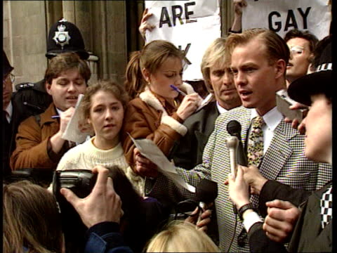 jason donovan wins libel case; england: london: high court: lms jason donovan out of court followed by mass of people and stands ready to read... - 文書による名誉棄損点の映像素材/bロール