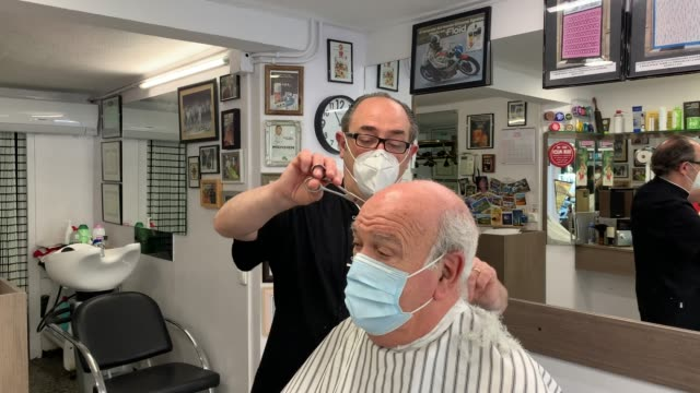 javier delwa cuts the hair of a customer as he wears a protective face masks at perruqueria vivanco barber shop which opened for the first day since... - opening event stock videos & royalty-free footage