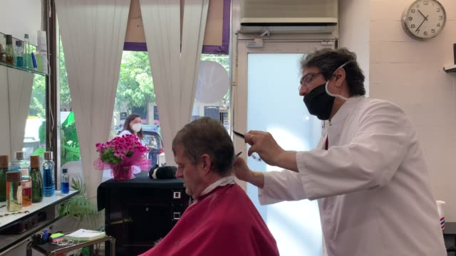 javier delwa cuts the hair of a customer as he wears a protective face masks at perruqueria vivanco barber shop which opened for the first day since... - small business stock videos & royalty-free footage