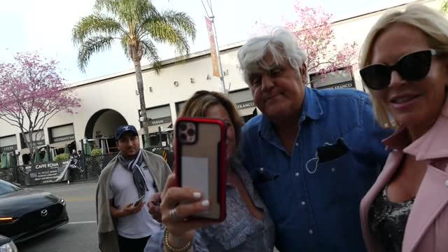 jay leno takes photos with fans while trying to take dinner home to his wife. - tv司会 ジェイ・レノ点の映像素材/bロール