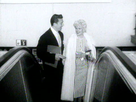 jayne mansfield and her husband ride an escalator at london airport - mickey hargitay stock videos & royalty-free footage