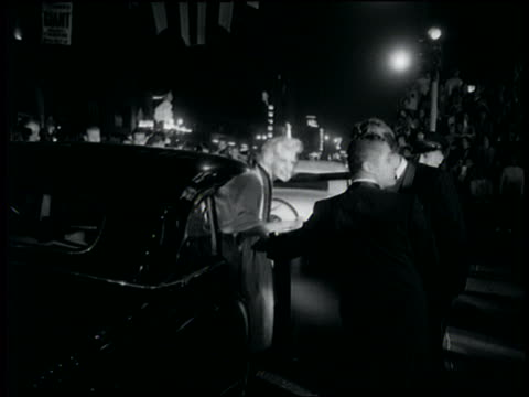 B/W Jayne Mansfield being helped out of car at night