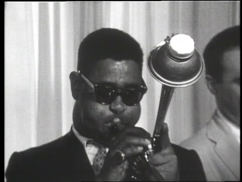 Jazz musician Dizzy Gillespie plays a trumpet with three musicians