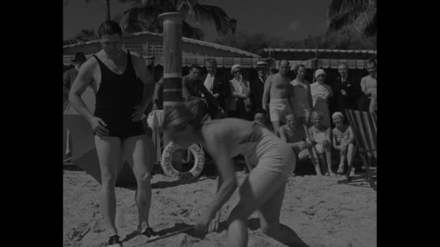 jean bauer and jimmie foxx stand on beach in bathing suits as crowd watches and bauer demonstrates golf club swing / bauer tees off / bauer and foxx... - golf club stock videos & royalty-free footage