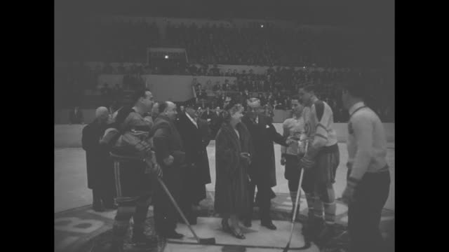 Jean Beliveau of the Montreal Canadiens and the captain of the Ottawa Senators escort actress Anne Baxter to the center of the hockey rink at the...