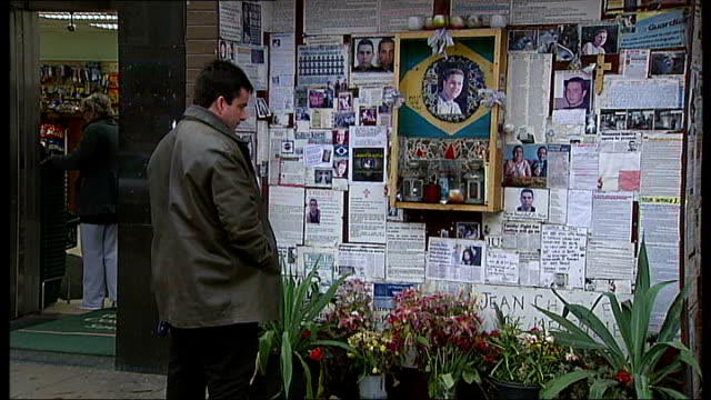 jury returns open verdict ext memorial shrine to jean charles de menezes at stockwell tube station man looking at shrine poster of menezes on shrine... - ストックウェル点の映像素材/bロール
