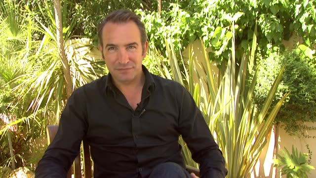 vídeos de stock, filmes e b-roll de jean dujardin on his character, how he develops through the story at the artist interview: 64th cannes film festival at all suites residences on may... - jean dujardin