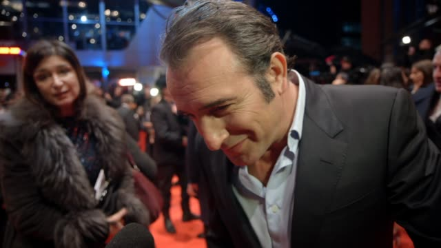 vídeos de stock, filmes e b-roll de jean dujardin talks about the film and the cast and being in berlin at 'the monuments men' red carpet at berlinale palast on february 8, 2014 in... - jean dujardin