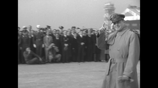 Jean MacArthur holds bouquet of flowers as she stands on tarmac near a United States Army Air Forces plane she and husband Douglas MacArthur are...