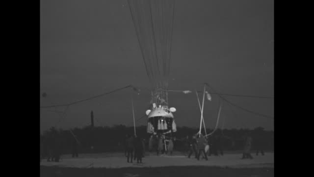 stockvideo's en b-roll-footage met jean piccard standing up in open hatch of gondola at night / jeannette piccard standing up in open hatch waving goodbye / tether holding balloon is... - hatch