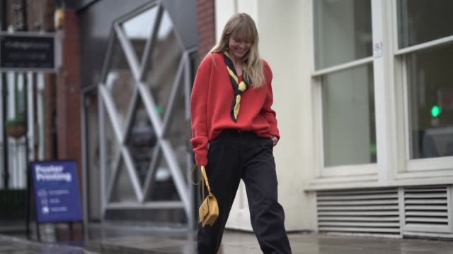Jeanette Madsen wears a black and yellow scarf an orange pullover black pants a yellow JW Anderson bag during London Fashion Week February 2019 on...