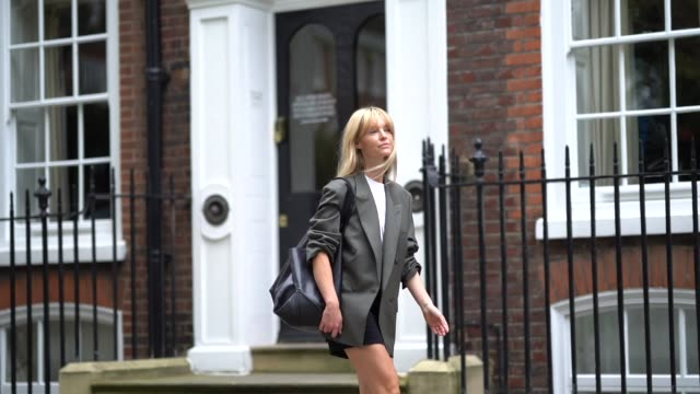 jeanette madsen wears an oversized blazer jacket with rolled-up sleeves, a black leather large celine bag, gray leather high heels boots, during... - gray jacket stock videos & royalty-free footage