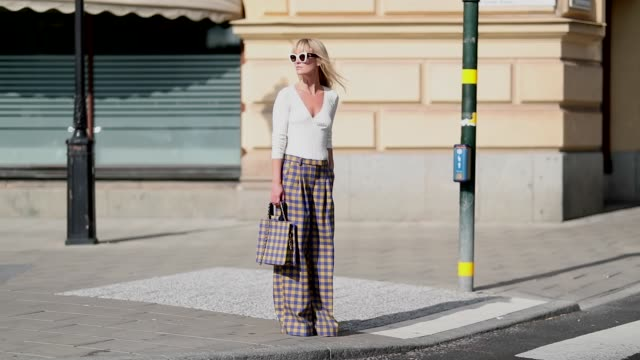 jeannette madsen wearing checked pants and bag, white v neck top seen during stockholm runway ss19 on august 29, 2018 in stockholm, sweden. - sunglasses stock videos & royalty-free footage
