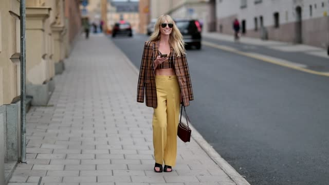 Jeannette Madsen wearing cropped checked top and jacket yellow pants during Stockholm Runway SS19 on August 30 2018 in Stockholm Sweden