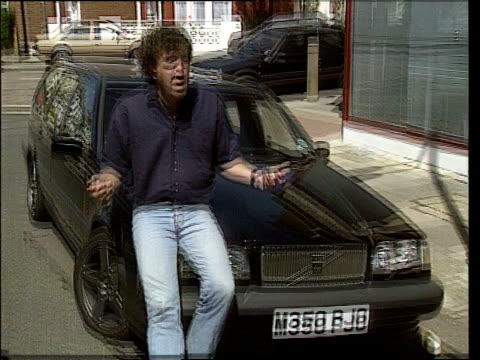 jeans are 'back in'; lib ext television presenter jeremy clarkson sitting on bonnet of car wearing blue jeans as interviewed lib england: london:... - ジェレミー クラークソン点の映像素材/bロール