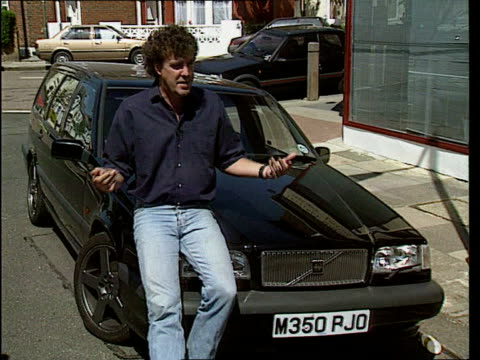 jeans are 'back in' lib television presenter jeremy clarkson sitting on bonnet of car wearing blue jeans as interviewed - jeremy clarkson stock-videos und b-roll-filmmaterial