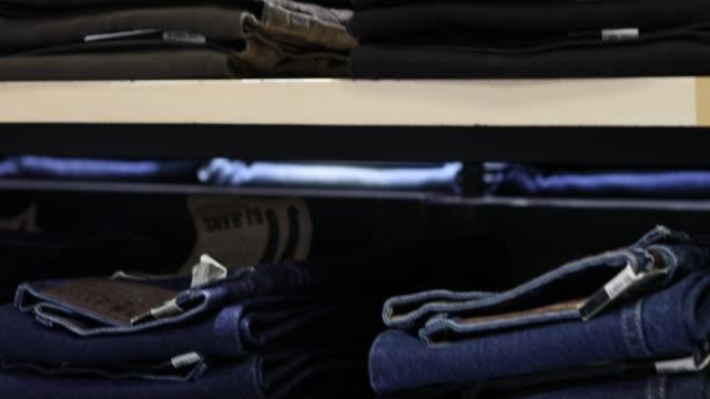 stockvideo's en b-roll-footage met jeans gestapeld op de planken. - jeans