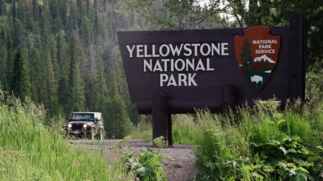 a jeep and motorcycles drive by the yellowstone national park welcome sign surrounded by forest and the rocky mountains - national park stock videos & royalty-free footage
