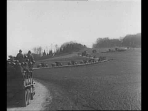 us jeep and trailer move on road in germany during world war ii bulletmarked mostly obscured road sign stands at left foreground / ls us military... - convoy stock videos & royalty-free footage