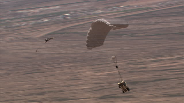 a-a jeep and white 1970's chevrolet sedan drop and parachutes toward desert; sedan lands (jeep landing not shot) - parachute stock videos & royalty-free footage