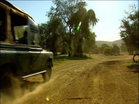 stockvideo's en b-roll-footage met jeep drives on dirt road in kenya camera pans up to sun and clear sky. - ruimte exploratie