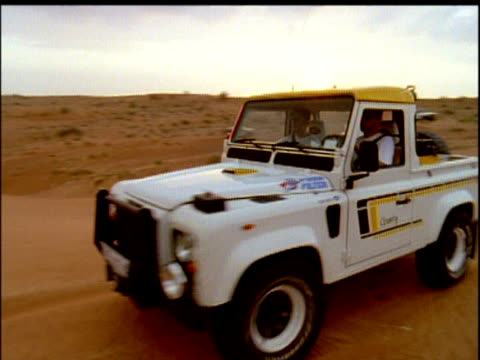 jeep drives past camera and down steep desert slope uae - steep stock videos & royalty-free footage