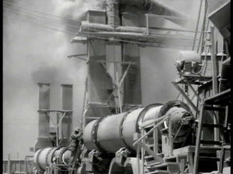 jeep moving forward out of area near asphalt plant. ext plant w/ drums turning smokestacks & smoke. workman standing by wheel possibly for releasing... - guam video stock e b–roll